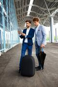 Picture of  two young businessmen talking on terminal background and holding - stock photo