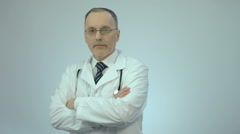 Successful confident doctor looking at camera with folded arms, clinic services - stock footage