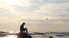 Inspired man on rock in the stormy sea writing - dolly shot Stock Footage