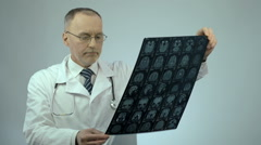 Unhappy doctor looking at MRI brain scan, upset about patient's health condition - stock footage
