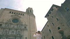 Girl take photo on phone Church of Sant Feliu in Girona Saint Felix , Spain Stock Footage