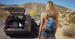 Young attractive woman comes across abandoned vehicle in the desert Stock Photos