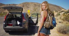 Young attractive woman abandons vehicle in the desert to steal a new ride Stock Photos
