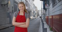 Charming young female barista taking a break in street alley Stock Photos