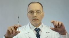 Doctor holding syringe and ampoule, prescribing effective medication to patient Stock Footage