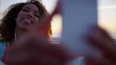 Attractive Ethnic African American female taking smart phone video on the beach Stock Footage