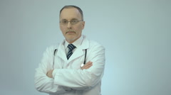 Successful confident doctor looking at camera with folded arms, clinic services Stock Footage