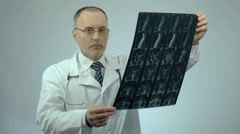 Serious physician checking injured spine scanning image, looking at camera Stock Footage