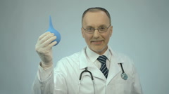Happy smiled proctology doctor showing rubber syringe and looking at camera Stock Footage