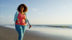 Ethnic African American female power walking by the ocean for toning exercise Stock Footage