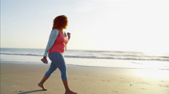 Ethnic African American female walking barefoot by the ocean at sunset  Arkistovideo