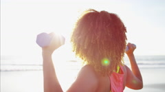 Ethnic African American female doing arm raises with toning weights for fitness Stock Footage