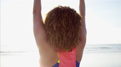 Ethnic African American female doing arm raises with toning weights on the beach Stock Footage