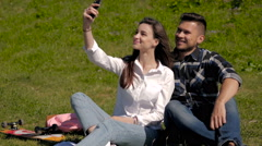 Young Couple Make Selfi Sitting on Grass In a Park Stock Footage