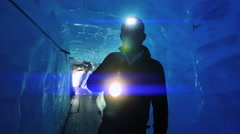 Silhouette of male scientist researching ice quality inside glacier. blue light Stock Footage