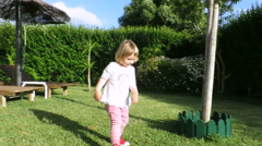 Blonde happy baby playing chasing camera in garden Stock Footage