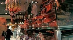 Beautiful girl choose jamon on market Stock Footage