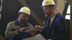 Two engineers in hardhats discussing in front of welding process Stock Footage