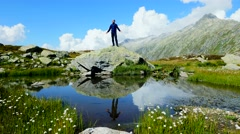 Male hiker standing on top of mountain raising hands. successful achievement Stock Footage