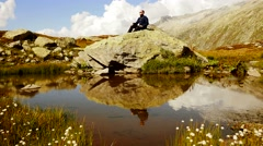 Hiker resting sitting on stone rock in mountain landscape enjoying achievement Stock Footage