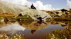 hiker resting on stone enjoying his achievement. mountain landscape scenery - stock footage
