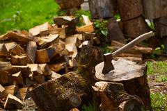 Old ax on log and firewood in the background Stock Photos