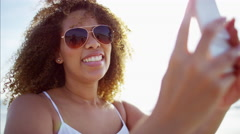 Afro hair African American female having fun on the beach taking a selfie photo Stock Footage