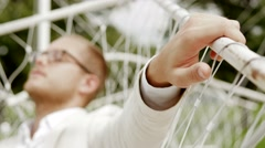 Man with closed eye relaxing outdoors sitting in swing. blurred background Stock Footage