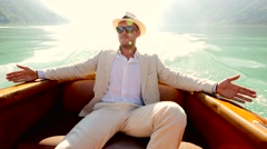 young caucasian man relaxing on boat deck wearing white casual suit - stock footage