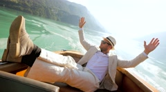 handsome single man in casual suit enjoying life on boat deck riding over lake - stock footage