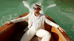 Relaxed single man in casual suit enjoying life on boat deck riding over lake Stock Footage