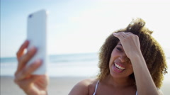 Afro hair African American female relaxed in a sundress on the beach for leisure Stock Footage