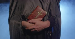 Monk, man  in Black Clothes, Black Hood,Bible in hands. Stock Footage