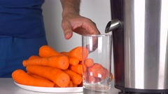 Man in blue clothes making carrot juice with shiny juicing machine. 4K shot Stock Footage
