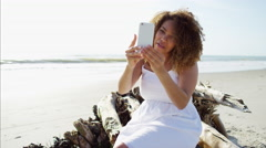 Afro hair Ethnic African American female sitting on driftwood by the ocean  Stock Footage