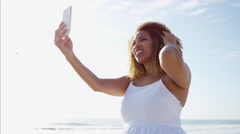 Afro hair African American female happy and taking a seascape photo with a phone Stock Footage
