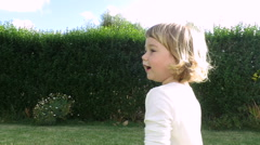 Cute baby two years jumping and talking in garden Stock Footage