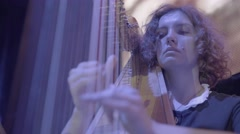 The harpist plays the harp during a concert Stock Footage