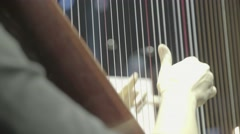 Hand of the harpist plays on the strings of the harp during a concert Stock Footage
