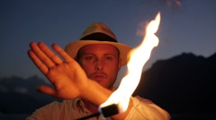 Man holding fire torch light playing with the flame in slow motion Stock Footage