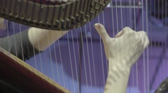Hands of the harpist playing the strings of the harp. Close-up Stock Footage