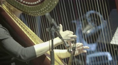Hands of the harpist while playing the harp on stage Stock Footage