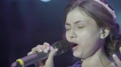 The girl singer sings on stage into the microphone (close-up) Stock Footage
