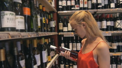 Woman blonde deciding what wine to buy and shopping in supermarket Stock Footage