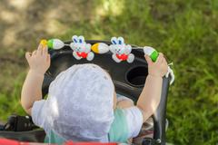 little girl sitting in a baby carriage - stock photo