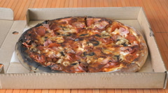 Closing cardboard box with a large pizza - stock footage