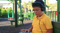 Young boy with  earphone using digital tablet at the park 2 Stock Footage