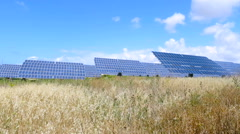 field with solar panels and blue sky with clouds - stock footage