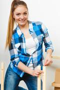 Woman assembling wooden furniture. DIY. - stock photo