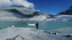 Man standing in front of glacier lake. mountain landscape background Stock Footage